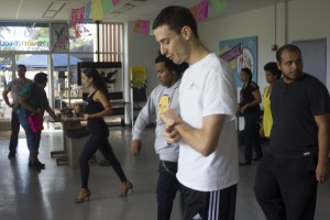 A dance instructors leads students trying to learn salsa
